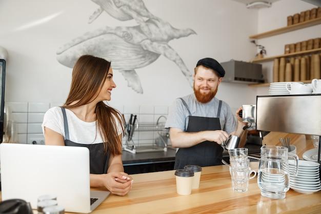 Concept d'affaires de café - jeune homme à barbe positif et jolie couple de baristes attrayants apprécient de travailler ensemble au café moderne