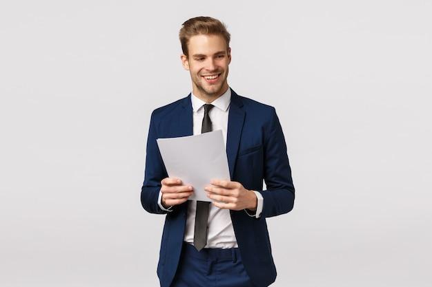 Concept d'affaires, d'élégance et de succès. bel homme d'affaires moderne élégant en costume classique, cravate, tenue de documents, papier et rire, sourire, détourner le regard, exprimer la confiance, fond blanc