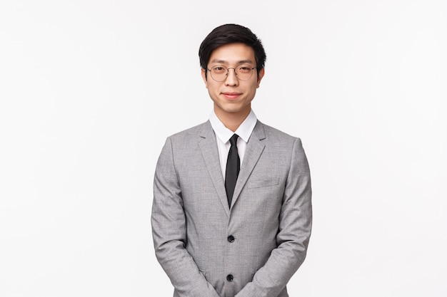 Concept d'affaires, de finances et de carrière. portrait de beau jeune homme professionnel asiatique en costume gris et cravate, regardez déterminé, souriant poliment, rencontrez les partenaires de l'entreprise sur le mur blanc