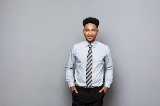 Concept d'affaires - heureux homme d'affaires afro-américain professionnel confiant posant sur le mur gris.
