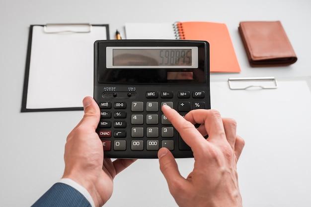 Concept d'affaires avec les mains à l'aide de la calculatrice