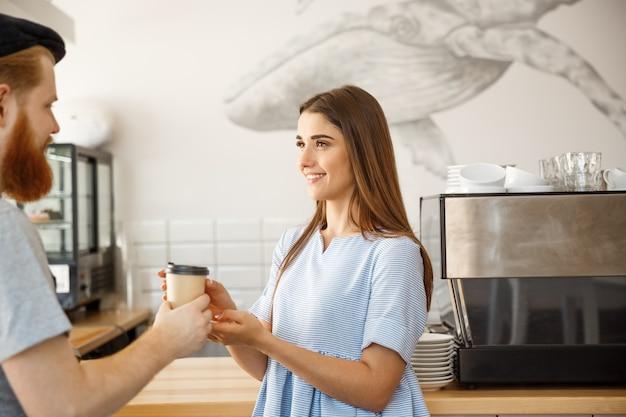 Concept d'affaires pour le café - le jeune barman à barbe intelligente aime discuter et donner de la tasse de café à la clientèle.