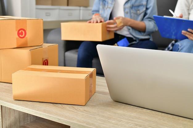 Concept d'affaires sme. les jeunes asiatiques emballent leurs paquets.