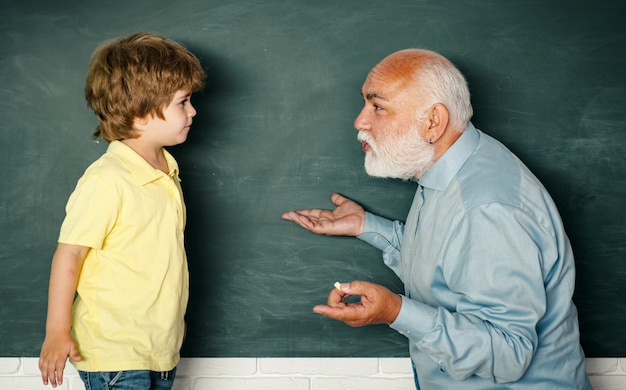 Concept d'un âge de la retraite. professeur d'école élémentaire et élève en classe. jeune garçon faisant son