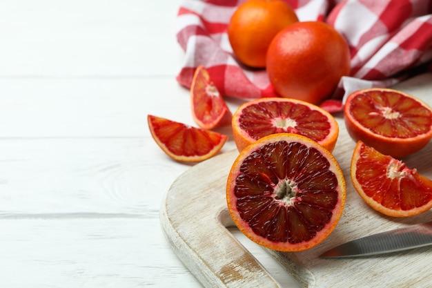 Concept d'agrumes avec des oranges rouges sur table en bois blanc