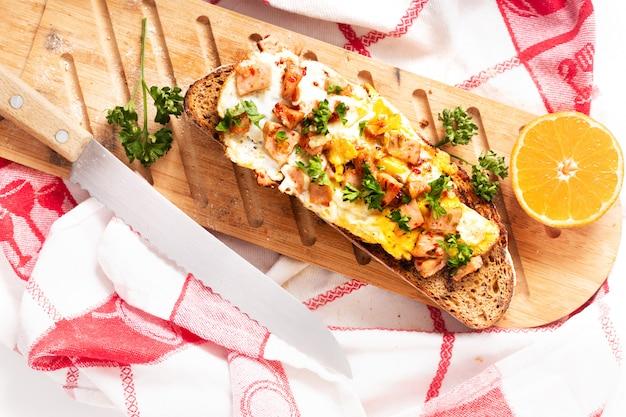 Concept alimentaire biologique français au levain grillé avec des œufs et du jambon sur une planche à découper en bois