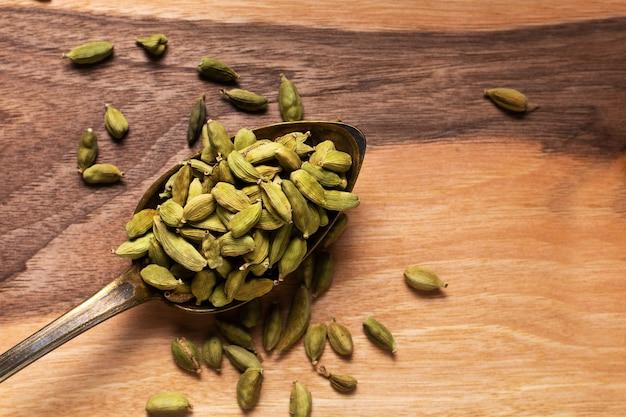 Concept alimentaire cardamome verte, cardamome, gousses de cardamum sur cuillère vinatge sur planche de bois avec espace de copie