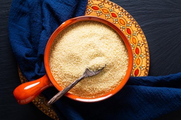 Concept alimentaire couscous cru bio dans un bol orange