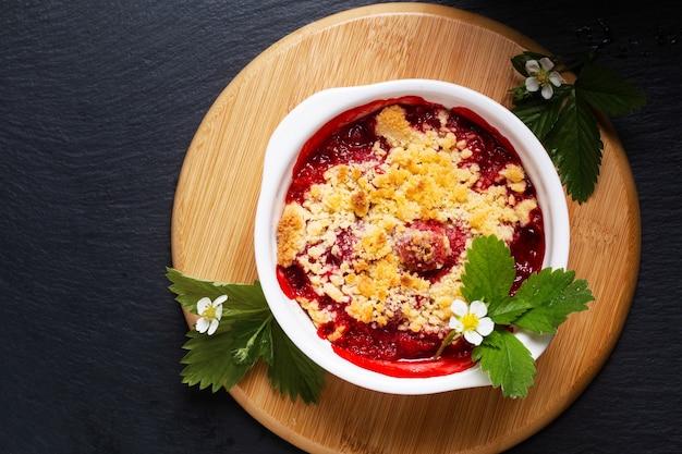 Concept alimentaire crumble aux fraises d'été rustique sur fond noir avec fond