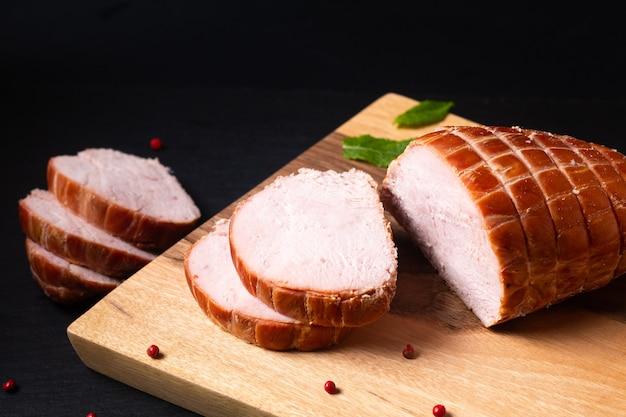 Concept alimentaire dinde biologique ou jambon salé de poulet allemand kassler ou kasseler sur planche de bois avec espace de copie