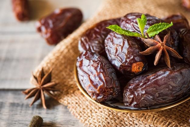 Concept alimentaire du ramadan. dates fruits et feuilles de menthe verte dans un bol