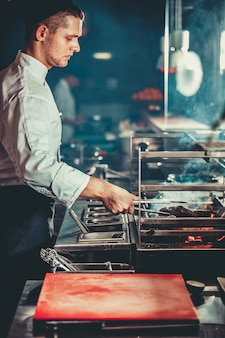 Concept alimentaire. jeune beau chef en uniforme blanc surveille le degré de rôtissage et transforme la viande