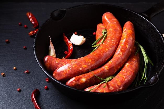 Concept alimentaire merguez saucisses épicées françaises dans une poêle en fer avec espace pour copie