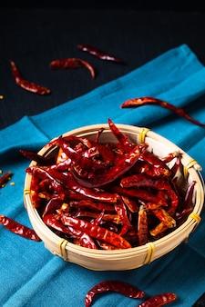 Concept alimentaire red hot chili séché, piments chili dans un plateau en osier de bambou sur fond noir avec espace de copie