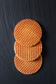 Concept alimentaire stroopwafel, sirop de caramel croustillant gaufres néerlandaises sur ardoise noire
