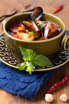 Concept alimentaire thai aigre curry rouge moules ananas kang kua hoi dans un bol en céramique verte sur fond de bois de serviette bleu avec espace de copie