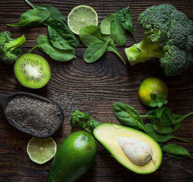Concept d'alimentation saine avec avocat, graines de chia et feuilles d'épinards, kiwi, brocoli sur table en bois