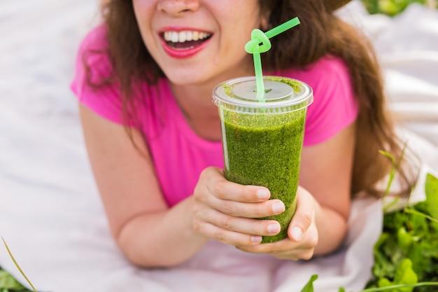 Concept d'alimentation saine, d'été et de personnes - une jeune femme s'amuse dans le parc et boit des smoothies verts lors d'un pique-nique en gros plan