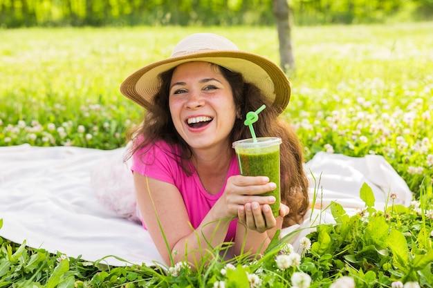 Concept d'alimentation saine, d'été et de personnes - une jeune femme s'amuse dans le parc et boit des smoothies verts lors d'un pique-nique