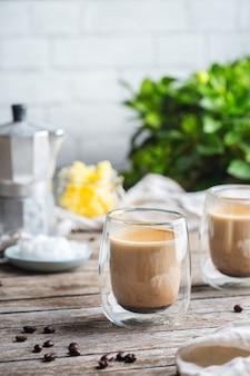 Concept d'alimentation saine et propre, céto, régime cétogène, table du petit-déjeuner le matin. café infusé pare-balles avec de l'huile de noix de coco biologique, du beurre de ghee, des grains de café. ambiance café cosy