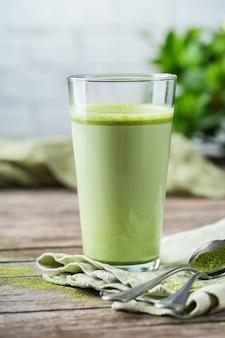Concept d'alimentation saine et propre, table du petit-déjeuner le matin. verre de thé vert matcha latte à la mode sur une table en bois. ambiance café cosy