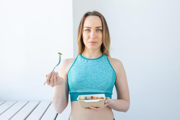 Concept d'alimentation saine, de régime et de remise en forme - jeune femme mangeant des légumes et de la viande après l'entraînement