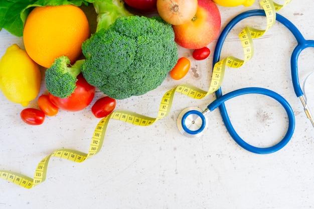 Concept d'alimentation saine, vagetables crus avec ruban à mesurer et stéthoscope sur tableau blanc