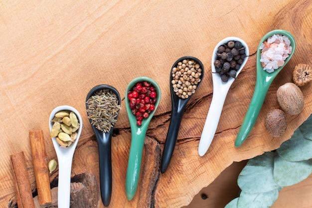 Concept d'aliments à base de plantes exotiques mélange d'épices biologiques dans une cuillère en céramique sur un fond en bois