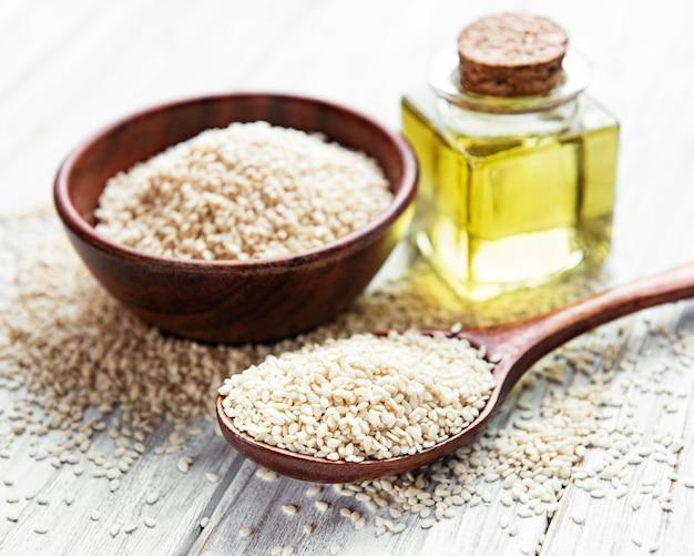 Concept d'aliments et de boissons sains. l'huile de sésame et les graines sur une table rustique.