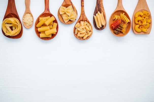 Concept d'aliments italiens et conception de menus. différentes sortes de pâtes sur un fond en bois blanc.