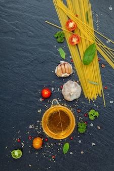 Concept d'aliments italiens et conception de menus. pâtes avec des ingrédients sur fond de pierre.