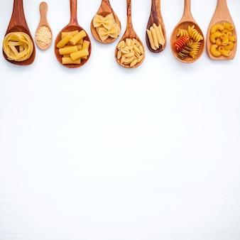 Concept d'aliments italiens et design de menus. différentes sortes de pâtes sur fond en bois blanc
