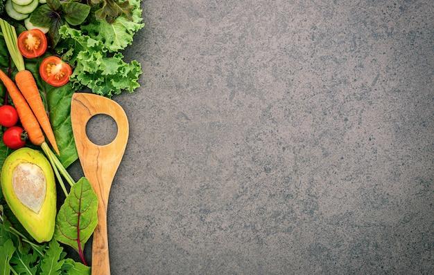 Concept d'aliments sains et de cuisine spatule en bois et légumes sur pierre sombre.