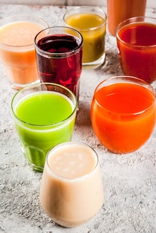 Concept d'aliments sains différents jus de fruits et légumes smoothie dans des verres