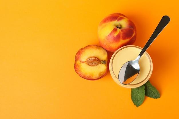Concept d'aliments sains avec du yaourt à la pêche sur fond orange