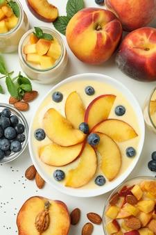 Concept d'aliments sains avec du yaourt à la pêche et des ingrédients sur fond blanc