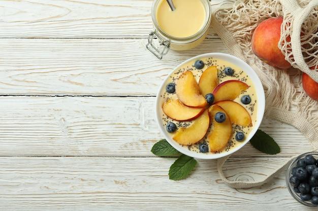 Concept d'aliments sains avec du yaourt à la pêche sur une table en bois blanc