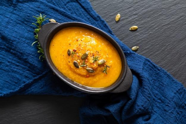 Concept d'aliments sains mélange chaud soupe de légumes et graines de citrouille dans une tasse en céramique noire
