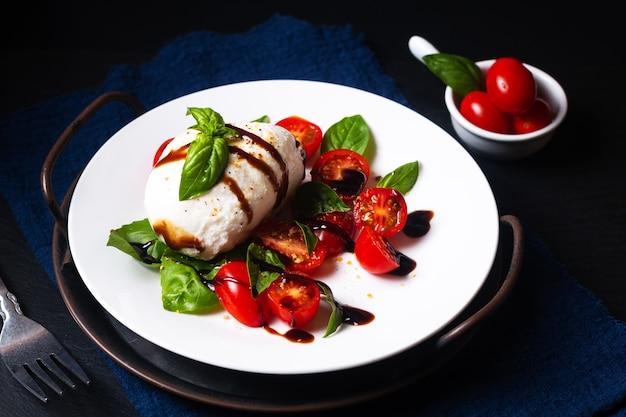 Concept d'aliments sains salade caprese rustique sur fond noir avec espace de copie