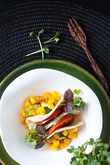 Concept d'aliments sains sandwich tacos salade microgreen vegan dans un bol en céramique blanche sur noir mat avec espace de copie
