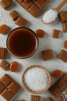 Concept d'aliments sucrés avec des morceaux de caramel, sel et sauce caramel sur fond texturé blanc