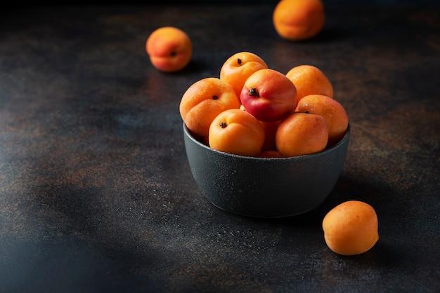 Concept d'aliments végétaliens sains avec des abricots sucrés dans une surface sombre, image de mise au point sélective