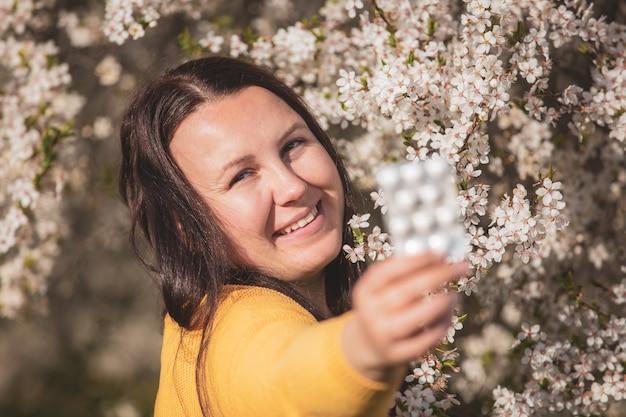 Concept d'allergie, jeune femme avec des pilules ou des médicaments contre la forte allergie en main devant la floraison d'un arbre au printemps, soins de santé