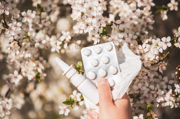 Concept d'allergie, jeune femme avec des pilules ou des médicaments et un spray nasal ou nasal contre la forte allergie en main devant la floraison d'un arbre au printemps, soins de santé