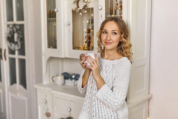 Concept d'ambiance festive de noël, belle jeune femme buvant du thé dans le salon décoré