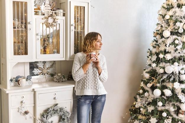 Concept d'ambiance festive de noël présenté par une fille buvant du thé