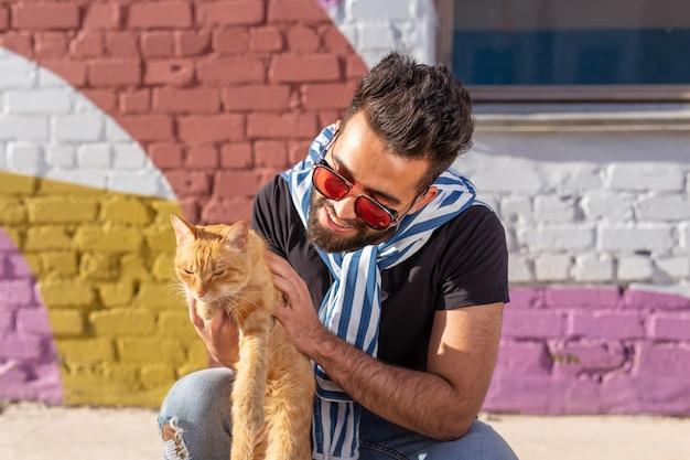 Concept d'amitié et d'animaux de compagnie - beau jeune homme avec un chat mignon à l'extérieur