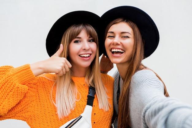 Concept d'amitié, de bonheur et de personnes. deux filles souriantes chuchotant des potins sur blanc