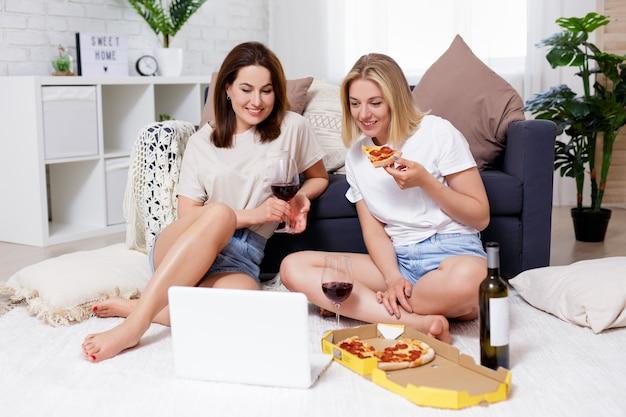 Concept d'amitié et de fête - deux jeunes belles amies mangeant de la pizza, buvant du vin et regardant un film sur un ordinateur portable dans un salon confortable