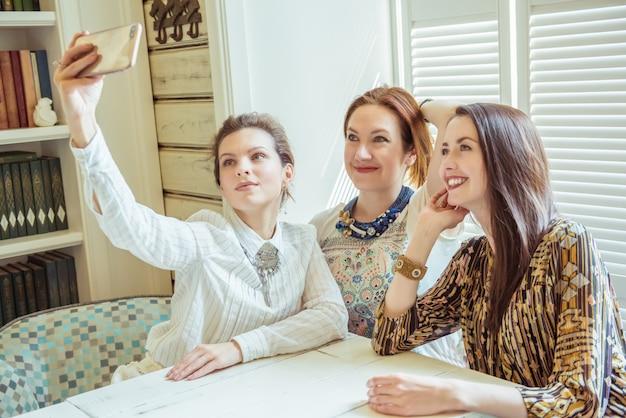 Concept d'amitié, de personnes, de fête et de technologie - amis heureux ou adolescentes avec smartphone prenant selfie